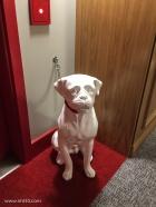 Ceramic dog leashed outside a room.